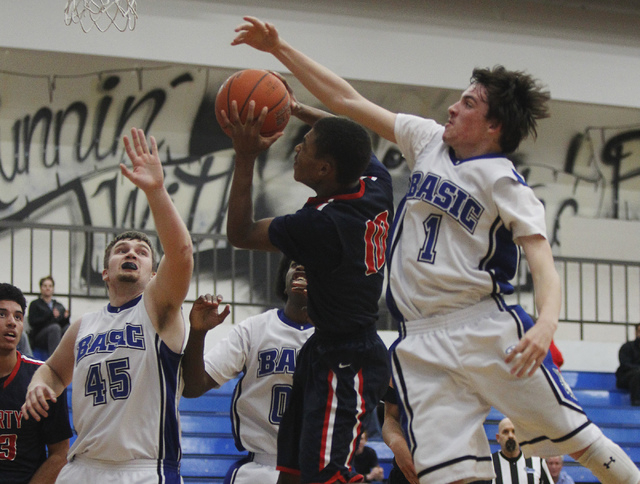 Basic's Jared Meacham (1) tries to block the shot of  Liberty's Jayven Hines-Stockton (10) during their basketball game in Henderson on Thursday, Jan. 30, 2014. (Jason Bean/Las Vegas Review-Journal)