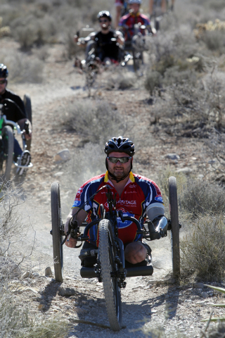 Army veteran John Masson, who lost three limbs after stepping on an improvised explosive device while serving in Afghanistan, leads a group of injured veterans through Red Rock Canyon near Blue Di ...