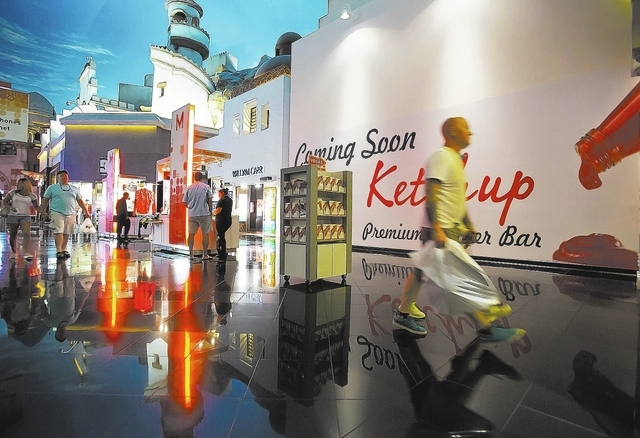 Shoppers walk past the future location of Ketchup Premium Burger Bar inside the Miracle Mile Shops at Planet Hollywood Resort and Casino on Thursday, Sept. 5, 2013. (Samantha Clemens/Las Vegas Rev ...