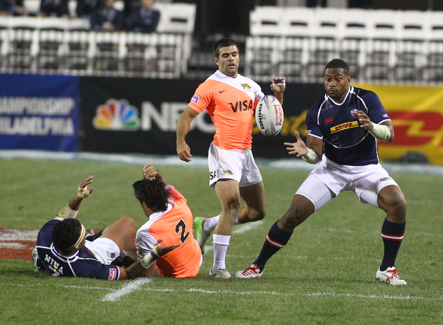 USA's Andrew Durutalo (8) receives a pass from Folau Niua (7) as Argentina's Joaquin Paz (2) makes the tackle during the first day of the USA Sevens rugby tournament at Sam Boyd Stadium in Las Veg ...