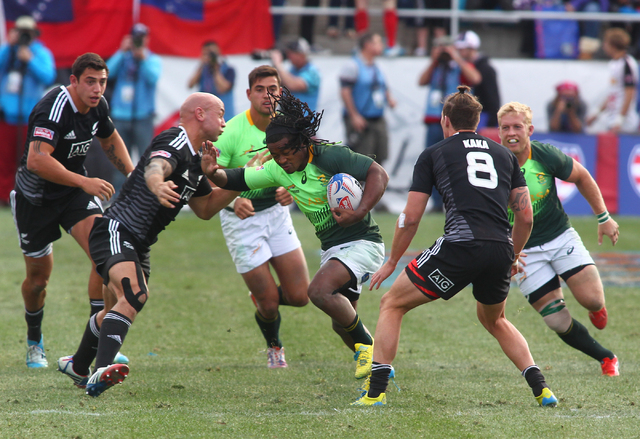 South Africa's Cecil Afrika pushes through New Zealand's DJ Forbes during the cup final of the USA Sevens rugby tournament at Sam Boyd Stadium in Las Vegas on Sunday. South Africa won 14-7 over Ne ...