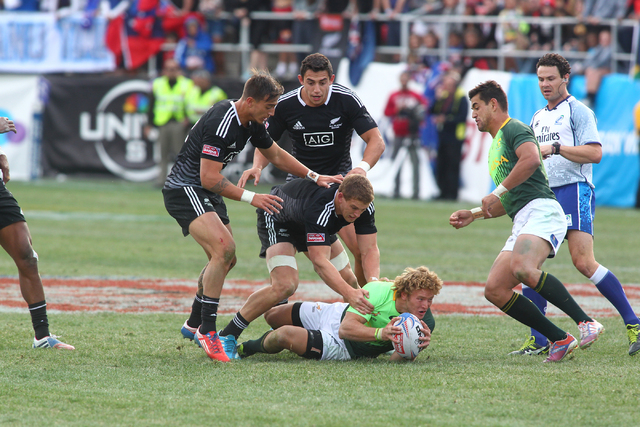 South Africa's Werner Kok looks to pass the ball to Chris Dry as New Zealand tackles during the cup final of the USA Sevens rugby tournament at Sam Boyd Stadium in Las Vegas on Sunday. South Afric ...