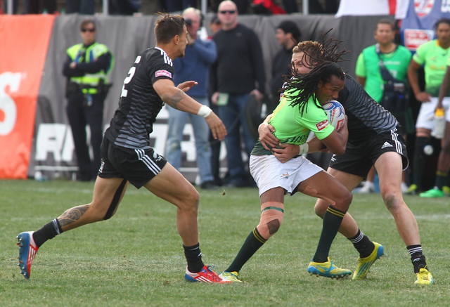 New Zealand's Tim Mikkelson, right, tackles South Africa's Cecil Afrika as Ambrose Curtis of New Zealand closes in during the cup final of the USA Sevens rugby tournament at Sam Boyd Stadium in La ...