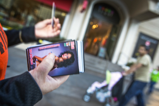 A woman passes out smut cards  in front of Paris Las Vegas hotel & casino, 3655 South Las Vegas  Boulevard, on Wednesday, Jan. 15, 2014.  Some businesses use the moniker Sin CityӠlabel  to g ...