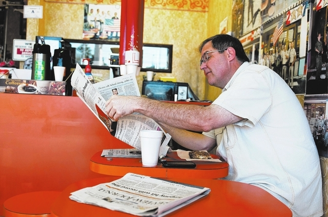 Customer Herb Thompson reads the newspaper at Donut Hut. Thompson has being a regular at the shop since owner Sothy Seang took over in 1991. (Erik Verduzco/View)