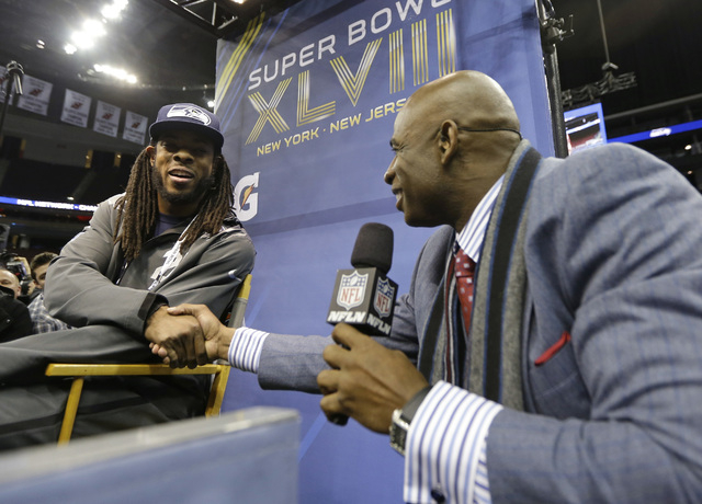Deion Sanders shakes hands with Seattle Seahawks' Richard Sherman during media day for the NFL Super Bowl XLVIII football game Tuesday, Jan. 28, 2014, in Newark, N.J. (AP Photo/Jeff Roberson)