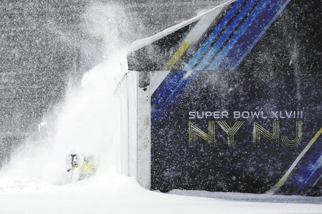 Workers shovel snow near a tent to be used as an access point into Super Bowl XLVIII as crews prepare MetLife Stadium in East Rutherford, N.J., during a snowstorm Tuesday. (AP Photo/Julio Cortez)