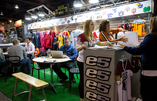 Kim Reiss, center, and Emily Jesrani, second from left, review collegiate sports apparel from E5 at the Sports Licensing and Tailgating Show at the Las Vegas Convention Center on Thursday. (Samant ...