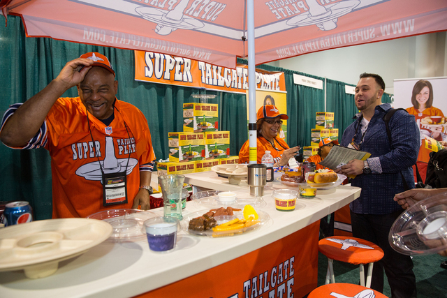"Larry Fenner, left, and Louise Coleman with ProAm 1 Sports Products joke with George Kokotis, right, while pitching the ""Super Tailgate Plate"" at the Sports Licensing and Tailgating Show at the La ..."