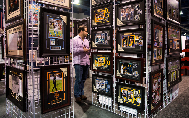 Marc Felicio with Worldwide Memorabilia stands among framed work during the Sports Licensing and Tailgating Show at the Las Vegas Convention Center on Thursday. (Samantha Clemens/Las Vegas Review- ...