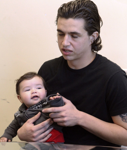Jeremy Grigis, of Las Vegas, holds his 6-month old son Jasper as he discusses his possible exposure to tuberculosis in Callister's office in Las Vegas, Friday, Jan. 10, 2014.   (Jerry Henkel/Las V ...