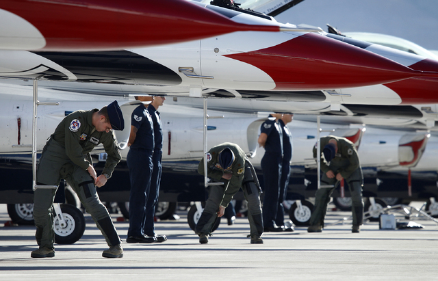 From left, Thunderbird pilots Maj. Joshua Boudreaux, Maj. Caroline Jensen and Maj. Curtis Dougherty suit up before taking off at Nellis Air Force Base in Las Vegas Friday, Jan. 10, 2014. Their Air ...