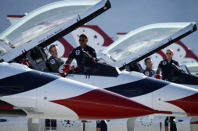 Thunderbird pilot Maj. Caroline Jensen smiles as Staff Sgt. Alex Reed helps her prepare in the cockpit of her plane before taking off at Nellis Air Force Base in Las Vegas Friday, Jan. 10, 2014. T ...