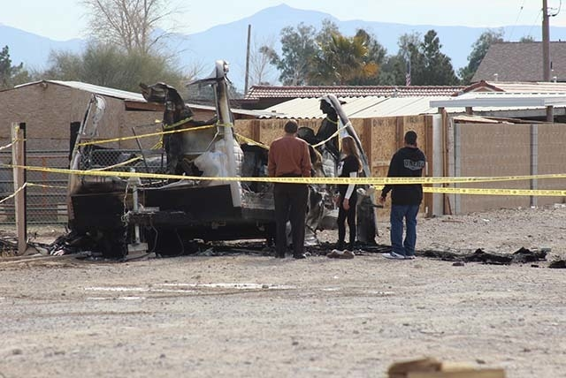The scene of a Sunday morning trailer fire that killed two people is examined. (Wesley Juhl/Las Vegas Review-Journal)