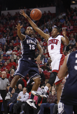 D.J. Fenner of Reno passes the ball by Christian Wood of UNLV during their game at the Thomas & Mack Center in Las Vegas Wednesday, Jan. 8, 2014. (John Locher/Las Vegas Review-Journal)