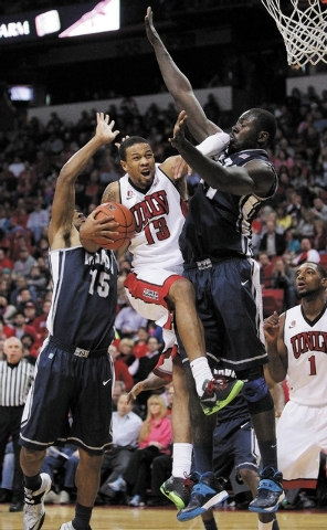 Bryce Dejean-Jones of UNLV tries for a shot against D.J. Fenner, left, and Ali Fall, right, of Reno during their game at the Thomas & Mack Center in Las Vegas Wednesday, Jan. 8, 2014. (John Locher ...