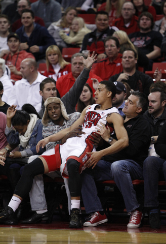 Kendall Smith of UNLV falls on fans in the front row during a game against Reno at the Thomas & Mack Center in Las Vegas Wednesday, Jan. 8, 2014. (John Locher/Las Vegas Review-Journal)