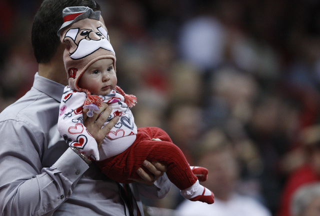 Russell Cleveland holds up his daughter Amelia during the UNLV game at the Thomas & Mack Center in Las Vegas Wednesday, Jan. 8, 2014. (AP Photo/Las Vegas Review-Journal, John Locher)
