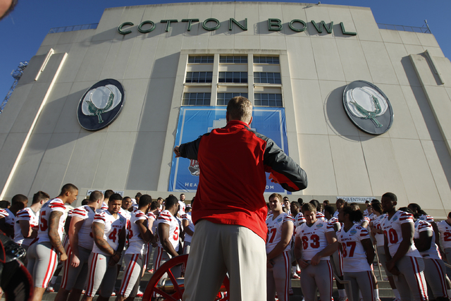 UNLV coach Bobby Hauck arranges his team for a photo Tuesday at the Cotton Bowl in Dallas, where the Rebels will face North Texas at 9 a.m. PST today in the Heart of Dallas Bowl. (John Locher/Las  ...