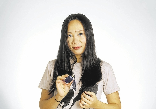 """Qian holds a bottle of perfume in a portrait that is part of Charles Mintz's """"Precious Objects"""" exhibit. Handwritten notes from the photo subjects, at left, accompany the portraits. (Courtesy)"""