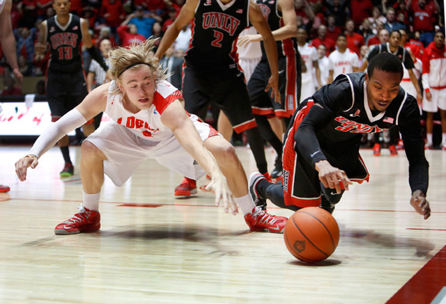 New Mexico's Hugh Greenwood, left, and UNLV's Deville Smith hit the floor for a loose ball in the second half of a game Wednesday in Albuquerque, N.M. UNLV won 76-73. (AP Photo/Eric Draper)