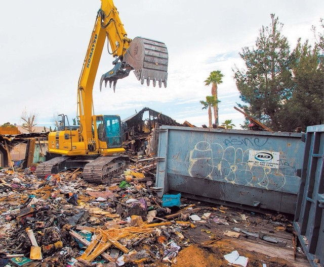 An excavator demolishes the house and contents at 1313 Esther Drive, Thursday Jan. 23, 2014. A Metro Police officer killed his wife and child before taking his own life at the location last year.  ...