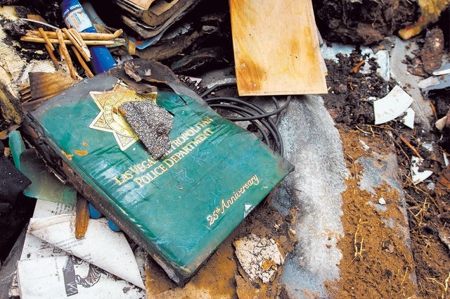 A Las Vegas Metropolitan Police 25th Anniversary book is seen as an excavator demolishes the house and contents at 1313 Esther Drive, Thursday Jan. 23, 2014. A Metro Police officer killed his wife ...