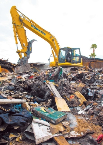 A Las Vegas Metropolitan Police 25th Anniversary book is seen in the foreground as an excavator demolishes the house and contents at 1313 Esther Drive, Thursday Jan. 23, 2014. A Metro Police offic ...