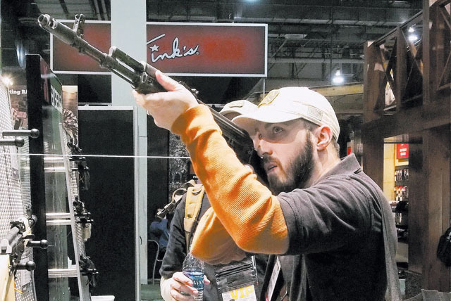 Ryan Horst of Martinsburg, W.Va., looks at an AK47-style rifle at the Arsenal booth at the 2014 SHOT Show at the Sands Expo Convention Center on Tuesday. Arsenal is based in Las Vegas.  (Jerry Hen ...