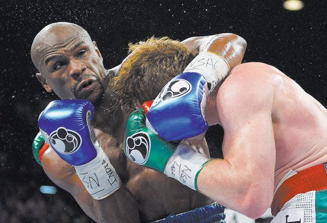 """Floyd Mayweather Jr., shown Sept. 14 subduing Canelo Alvarez at the MGM Grand, arrives in South Africa today for a six-day visit that government officials hope will help """"resuscitate"""" boxing in th ..."""
