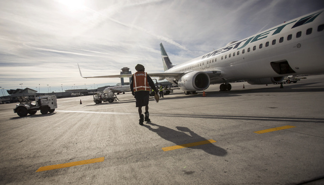 A ground crew at McCarran International Airport prepares a WestJet for takeoff on Tuesday, Dec. 24, 2013. The  Canadian airline company will become the first foreign airline to take one million pe ...