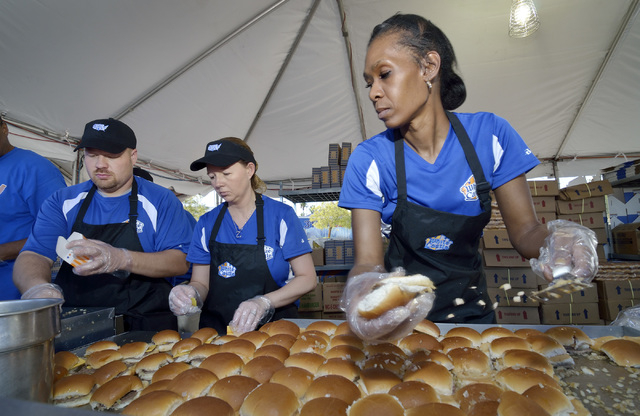 Leslie Baggett, right, makes White Castle burgers as Kathey Gunderson, center, and James Helton help with finishing touches and packaging during the Las Vegas Foodie Fest in the parking lot of the ...