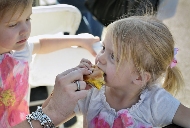 Ayla Madsen, right, takes a bite of a White Castle burger as her twin sister Alexa looks on during the Las Vegas Foodie Fest in the parking lot of the Silverton hotel-casino at 3333 Blue Diamond R ...