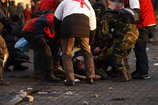 An anti-government protester that suffered a gunshot wound is being helped by fellow protesters and medical workers at Independence Square in Kiev, Ukraine, Thursday, Feb. 20, 2014. Fearing that a ...