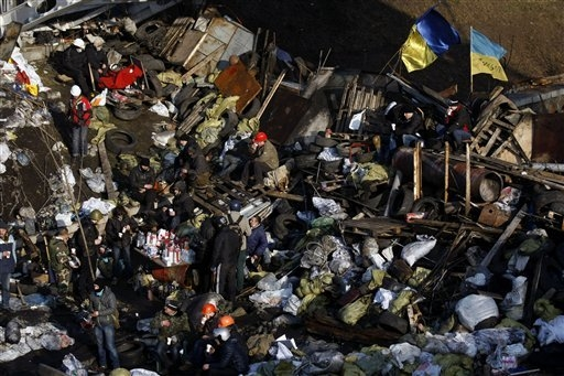 Anti-government protesters man a barricade at  Independence Square in Kiev, Ukraine, Thursday, Feb. 20, 2014. Fearing that a call for a truce was a ruse, protesters tossed firebombs and advanced u ...