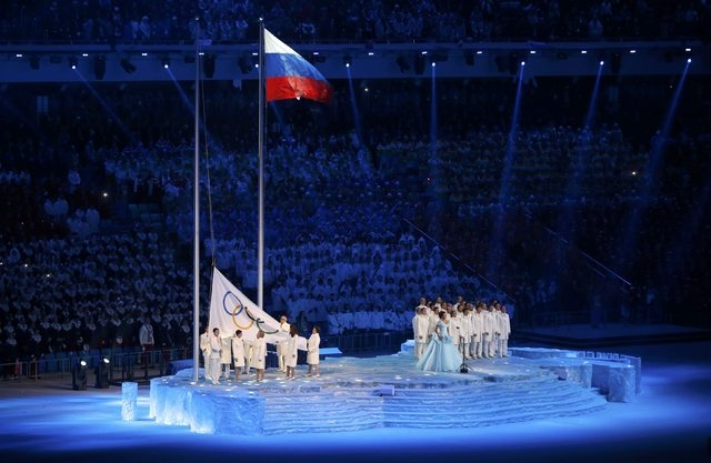 The Olympic flag is raised next to the flag of Russia during the opening ceremony of the 2014 Sochi Winter Olympics, February 7, 2014. REUTERS/Mark Blinch (RUSSIA  - Tags: OLYMPICS SPORT)