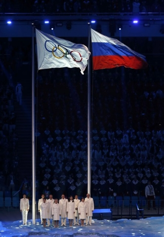 Participants stand after the Olympic flag (L) was raised during the opening ceremony of the 2014  Sochi Winter Olympics, February 7, 2014.  REUTERS/Lucy Nicholson (RUSSIA  - Tags: OLYMPICS SPORT)