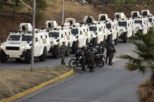 National Guard anti-riot vehicles wait in line during a protest against Nicolas Maduro's government in Caracas February 16, 2014. A Venezuelan opposition leader wanted by police in connection with ...