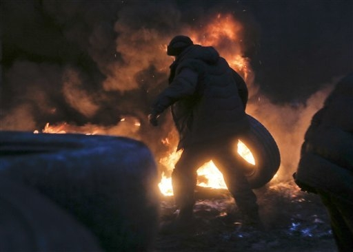 An activist carries a tyre at the burning barricades close to Independence Square, the epicenter of the country's current unrest, in Kiev, Ukraine, Thursday, Feb. 20, 2014. Fierce clashes between  ...