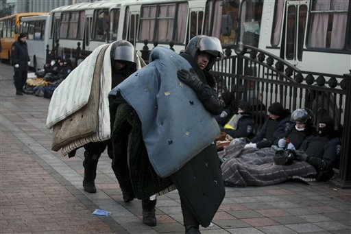 Police officers carry mattresses to take a rest at Ukraine's parliament in Kiev, Ukraine, Thursday, Feb. 20, 2014. Ferocious street battles between protesters and police in the Ukrainian capital h ...