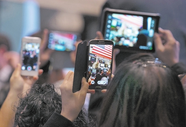 In this Monday, Nov. 4, 2013, file photo, visitors on the floor of the New York Stock Exchange use their smartphones and tablet devices to photograph the opening bell ceremonies. 2013 was a great  ...