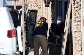 FBI agents board up a glass door that was broken when agents served a search warrant at Leon Benzer''s offices in September 2008. Benzer is among nearly 40 conspirators charged in a scheme to tak ...