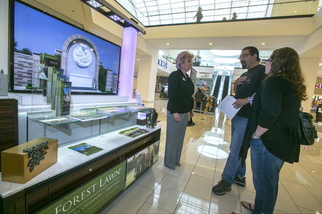 Forest Lawn regional sales manager Hilda Carabes, left, shows Mark Sanchez and his wife, Lea'Anne, at the Forest Lawn stand at the Glendale Galleria mall in Glendale, Calif. Forest Lawn, famous as ...