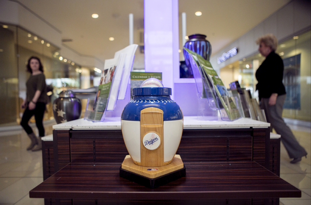 A Los Angeles Dodgers baseball sports cremation urn is displayed at the Forest Lawn stand at the Glendale Galleria mall in Glendale, Calif. Forest Lawn has begun staffing outlets at shopping malls ...