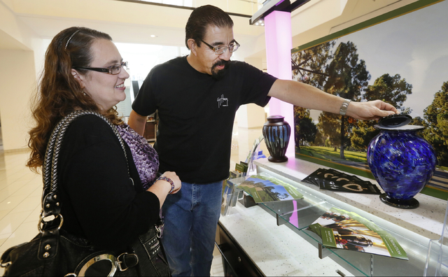 Mark and Lea'Anne Sanchez look at a Los Angeles Dodger's theme cremation urn at the Forest Lawn stand at the Glendale Galleria mall in Glendale, Calif. Forest Lawn has begun staffing outlets at sh ...