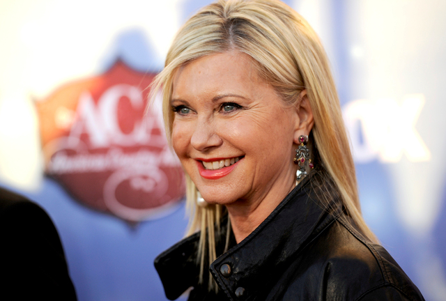 In this Tuesday, Dec. 10, 2013, file photo, Olivia Newton-John arrives at the American Country Awards at the Mandalay Bay Resort & Casino, in Las Vegas. The 65-year-old singer and actress announce ...