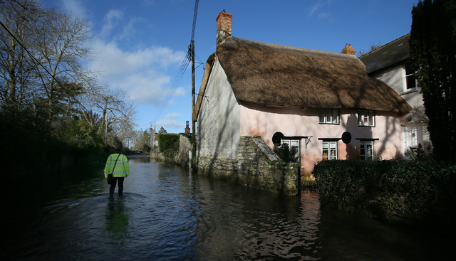 In this photo taken Sunday Feb. 2, 2014, an emergency support worker wades through floodwater in Thorney in Somerset, England. Here on the Somerset Levels _ a flat, marshy region of farmland dotte ...