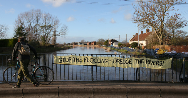 """In this photo taken Sunday Feb. 2, 2014, a cyclist goes over a bridge where locals have put up a sign 'Stop the Flooding - Dredge the Rivers"""" on the River Parrett, at Barrow Mump,  in Somerse ..."""