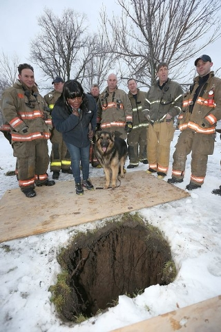 Buffalo, N.Y. Rescue 1 firefighter Michael Paveljack, left,  Mattie Moore, second from,left, and her dog Mack stand by the sink hole where Paveljack rescued Mack on Sunday Feb. 2, 2014 in Buffalo, ...