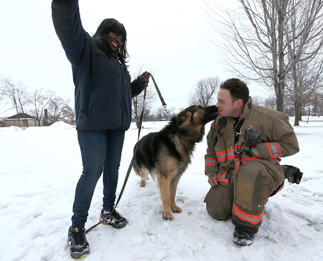 Rescue 1 firefighter Michael Paveljack, right, gets a kiss from Mack the dog he rescued  from a sink hole in Buffalo,  N.Y. Sunday Feb. 2, 2014.  Mack fell into the sink hole while he was being wa ...